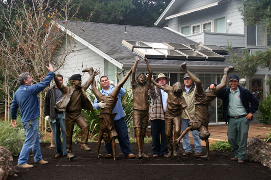 Picture of men at work posing with bronze statue